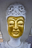 Carved head on post with gold leaf, Thailand.