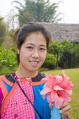 Young Lisu tribal woman wearing traditional dress and holding pink flowers