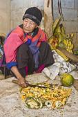 Old woman, 86, in traditional dress of Lisu Tribe, chops papaya