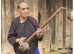 Elderly Lisu man shows off simple stringe banjo made of teak & redwood and covered with iguana skin.