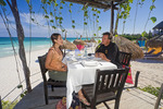 Man and woman have relaxing lunch on the beach of a resort at Riviera Maya, Yucatan Peninsula of Mexico.