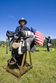 Man portrays a first sergeant from the 1880s, leaning on his horse saddle with an American Flat behind him at Living History fair on the grounds of Old Mission State Park in Cataldo, Idaho.