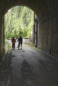 Man and woman stand with their bicycles at the end of the Taft Tunnel, the longest tunnel on the Hiawatha Trail, Idaho, USA.