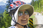 Woman cyclist wearing floppy sun hat under her bicycle helmet has a fellow cyclist reflected in her sun glasses on the Hiawatha Trail, a cycling and hiking trail in Idaho, USA.
