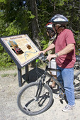 Man and woman cyclists read one of the historical plaques on the Hiawatha Trail, Idaho, USA.