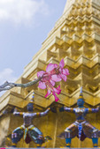 Closeup of blooming flower against guardian mythical demons supporting the base of a golden Chedi at the temple of the Emerald Buddha at The Grand Palace in Bangkok, Thailand.