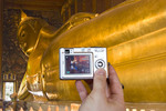 Tourist takes digital picture of giant reclining Buddha statue in Wat Pho, Bangkok, Thailand.