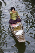 Woman vendor at Damnoen Sakuak floating market in a khlong boat.