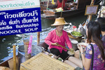 Woman vendor in boat sells soup to young woman at Damnoen Sakuak floating market