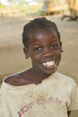 Young girl smiles for the camera in her village in Zambia. The kids are thrilled to see themselves in a camera's LCD screen.