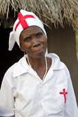 Elderly woman is native healer for village and poses in her nurse outfit.
