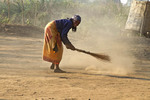 Young woman sweeps ground with a straw broom in her village. Zambia.