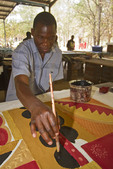 Man paints African pattern onto cloth at Tribal Textiles, a workshop in Zambia, Africa.