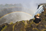 Young woman sits at the edge of Victoria Falls to view double rainbow.