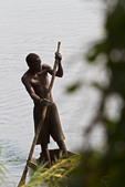 Local fisherman poles his dugout canoe along the bank of the Zambezi River in Livingstone, Zambia.