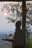 Waiter serves a cold glass of beer as the sun set at a safari lodge in Livingstone, Zambia, Africa.