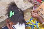 Woman braids hair of friend at craft village in Zambia.
