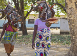 Women with babies in slings  carry firewood for cook fires in their village, Kawaza, Zambia, Africa.