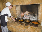 Cook prepares stews at fireplace an example of gourmet dining at ski resorts.