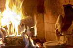 Raclette wheel of cheese melts by fireplace, an example of gourmet dining at ski resorts.