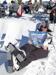 Skier reads her ski trail map and relaxes on a beach chair onslop at Mammoth Mountain ski resort, California, USA