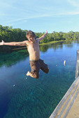 Young man jumps into Wakulla Spring from high platform, Wakulla Springs State Park, Florida, USA.