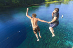 Young man and woman hold hands and jump into Wakulla Spring from high platform, Wakulla Springs State Park, Florida, USA
