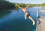 Young man dives into Wakulla Spring from high platform, Wakulla Springs State Park, Florida, USA