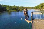 Young woman jumps into Wakulla Spring from high platform, Wakulla Springs State Park, Florida, USA