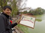 Local boys paint popular red bridge over Hoan Kiem Lake in the historical center of Hanoi, Vietnam.