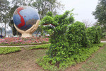 Dragon topiary sits by globe of the world in front of Hoan Kiem Lake, Vietnam.