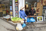 Woman on bicycle with vegetables for sale in in the