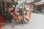 Man on bicycle with baskets for sale in the