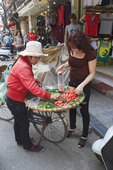Woman buys tomatoes from a street vendor in the old quarter of Hanoi, Vietnam.