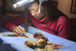 Young woman sews delicate embroidery into a landscape 'painting' at Hanoi's Ethnology Museum.