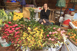 Woman sells flowers in Hom Market, in Hanoi's Old Quarter, Vietnam.