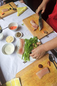 Celebrity chef Madam Pham Thi Tuyet helps student prepare steamed catfish in cooking class, Hanoi, Vietnam.