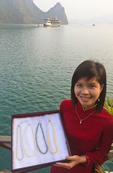 Woman shows pearl necklaces of varying colors at Pearl Tourist Village floating in Ha Long Bay, Vietnam