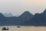 Sun sets behind rugged limestone hills in Ha Long Bay, Vietnam.