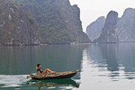 Small traditional skiff rowed using foot powered oars in Ha Long Bay, Vietnam.