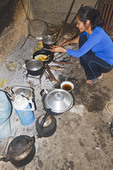 Local woman cooks lunch in her rustic kitchen on Cat Ba Island, Ha Long Bay, Vietnam.