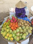 Woman sells fruit at market along Thu Bon River, Hoi An, Vietnam.