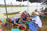 Women sell food and flowers at market along Thu Bon River, Hoi An, Vietnam.