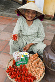 Elderly woman sells trinkets and whistles on the streets, Hoi An, Vietnam.