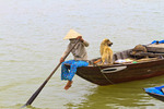 Local residents work their way down Thu Bon River in traditional boat, Hoi An,  Vietnam.