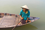 Elderly woman wearing Vietnamese cone hat in traditional boat on the Thu Bon River, Hoi An, Vietnam.
