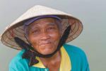 Closeup of elderly woman wearing typical Vietnamese cone hat. Hoi An, Vietnam.
