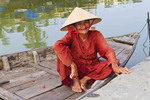 Elderly woman in traditional boat on the Thu Bon River, Hoi An, Vietnam.