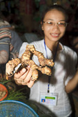 Woman shows ginger root for sale in market along Thu Bon River, Hoi An, Vietnam.