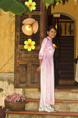 Lovely young woman in traditional Vietnamese dress (Ao dai) stands outside restaurant in Old Town, Hoi An, Vietnam.